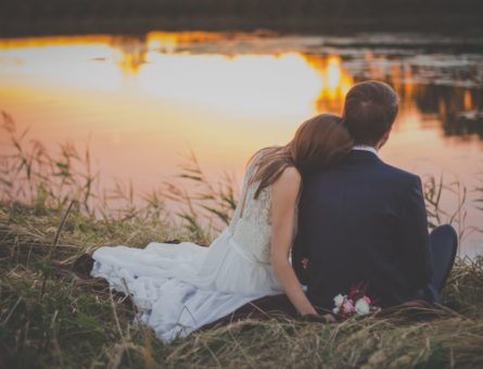 wedding-couple-sitting-on-green-grass-in-front-of-body-of-70737